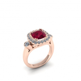 14kt rose gold ring with a cushion-shaped ruby center stone and a halo round round brillinat cut white diamonds, and two bezel set diamonds on either side.