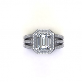 14kt white gold engagement ring with an emerald cut center diamond that has a halo with round brilliant cut diamonds, the shank is three bands with bead set round brilliant cut diamonds connected at the halo.