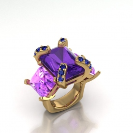 18kt yellow gold three-stone ring with amethyst and pink topaz emerald cut stones, and on the prongs of the amethyst center there are blue sapphires.